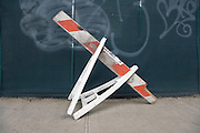 broken traffic warning sawhorse placed on the sidewalk pavement