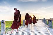 Buddhist monks strolling on U Bein bridge