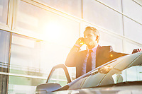 Portrait of mature attractive businessman talking on smartphone while standing outside the car