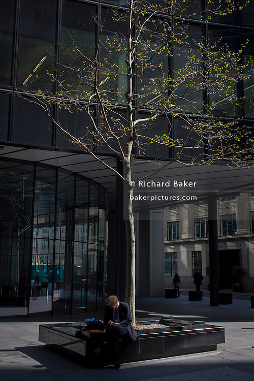Businessmen sits beneath an urban tree in the City of London.