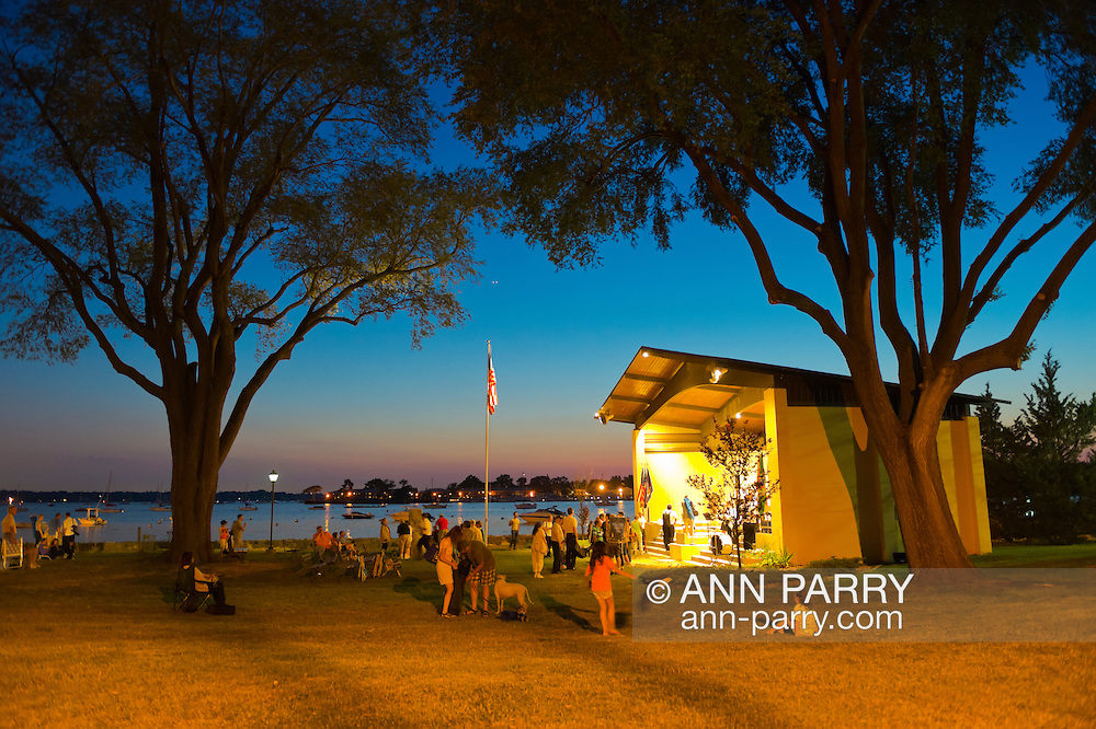 Port Washington, New York, U.S. - July 11, 2014 - Audience gets ready to leave at end of night time outdoors band concert at John Philips Sousa Memorial Band Shell, at Sunset Park on Manhasset Bay in the North Shore village on Long Island Gold Coast.