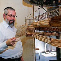 Streit's Matzoh, NYC. The matzoh is taken from the oven on a conveyor belt and sorted into stacks of 11 pieces, which are placed in wire baskets. The baskets will carry the pre-sorted matzoh to the packaging room where each stack will fill an 11 0z. box. Rabbi Kirscher checks the matzoh as it comes out of the oven.