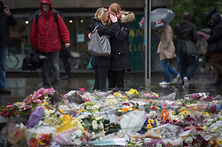 © Licensed to London News Pictures. 06/06/2017. London, UK. Emotional members of the public look at Floral tributes placed at the scene at London Bridge following a terrorist attack in Saturday evening. Three men attacked members of the public  after a white van rammed pedestrians on London Bridge. Ten people including the three suspected attackers were killed and 48 injured in the attack. Photo credit: Ben Cawthra/LNP
