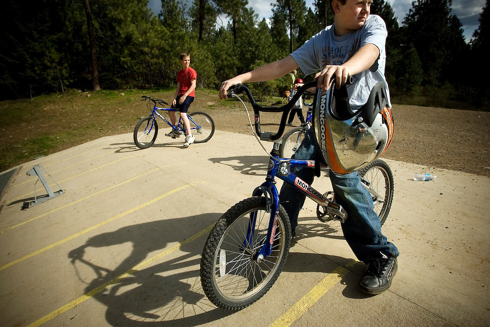 JEROME A. POLLOS/Press..Michael Peterson, 12, foreground, and Nate Wallsinger, 13, wait for other riders to make their way to the starting line at the BMX track at Cherry Hill after school Wednesday.