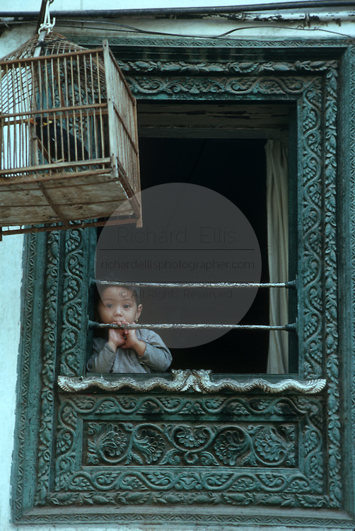 A young child looks out from an carved window overlooking Durbar Square in Kathmandu, Nepal.