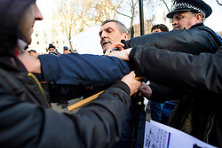 © Licensed to London News Pictures. 05/12/2016. London, UK. Police intervene as a fight breaks out between an anti Brexit supporter (left) and a pro Brexit supporter (centre), outside the Supreme Court  in Westminster, London on the first day of a  Supreme Court hearing to appeal against a November 3 High Court ruling that Article 50 cannot be triggered without a vote in Parliament. Photo credit: Ben Cawthra/LNP