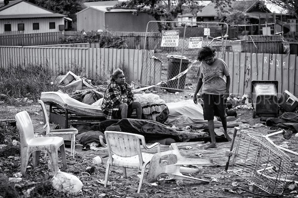 Sussanne Charmawina and Jacquelin waking up in their new camp, at the other side of the fence, as the condemned house they used before in Kennedy Hill, has now been demolished. Till this day this camp is still being used by many homeless people. Kennedy Hill, Broome, Western Australia. ©Ingetje Tadros/Diimex