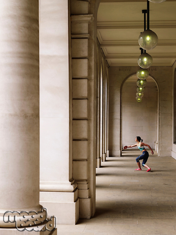 Female athlete throwing discus in portico side view