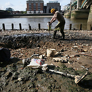 Mudlarker Ian Smith digs a hole as he looks for items on the bank of the river Thames in London, Britain May 22, 2016. When the river Thames is at low tide, mudlarkers scour the shore for historical artefacts and remains from there City of London's ancient past. Finds can date back to Roman times to when the city was found up until more recent times. Anyone can walk along the river and look for finds, but the uses of metal detectors and digging is restricted. Mudlarkers need to be licences by the Port of London Authority. All find should be register with the Museum of London. REUTERS/Neil Hall