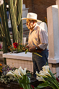 An elderly Mexican man decorates the gravesite of his wife for Day of the Dead festival known in Spanish as Día de Muertos at the old cemetery October 31, 2013 in Xoxocotlan, Mexico. The festival celebrates the lives of those that died.