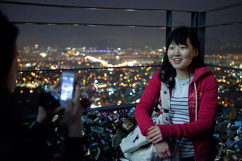 Junge Dame wird in abendlicher Stimmung auf der unteren Aussichtsplattform des N Seoul Towers in der koreanischen Haupstadt - umringt mit W&uuml;nschen versehenen Schl&ouml;ssern -fotografiert. Der N Seoul Tower ist ein der &Ouml;ffentlichkeit zug&auml;nglicher Fernsehturm in der s&uuml;dkoreanischen Hauptstadt Seoul. Der 236,7 Meter hohe Turm steht auf 243 m &uuml;. N.N. des Berges Namsan.<br /> <br /> Young woman gets  photographed during an evening mood at the lowest observation deck of the N Seoul Tower surrounded by lockers. N Seoul Tower is a communication tower located in Seoul, South Korea. Built in 1969, and opened to the public in 1980, the tower measures 236.7 m (777 ft) in height (from the base) and tops out at 479.7 m (1,574 ft) above sea level.