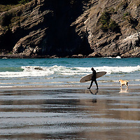 A surfer and his dog are on their way out to the surf, his full body wetsuit attests to the temperature of the water on this spring day along the Oregon coast.  The colors of the cliffs contrast nicely with the blues, greens, and whites in the water and waves.