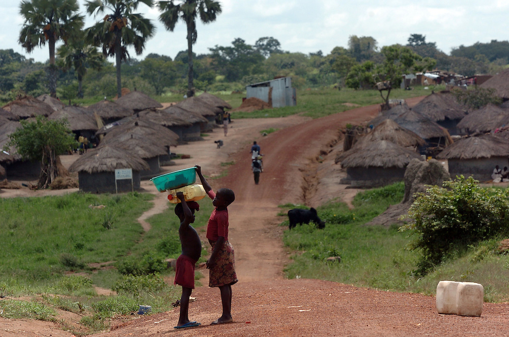 Children carry water to their homes in Tetugu Camp in Gulu District, north Uganda October 7, 2006. Tetugu Camp, with a population of approximately 22,000, is one of 76 camps outside the town of Gulu created for internally displaced people in north Uganda. Since the war began in 1987 over 2 million people have moved from their village homes to camps close to the town of Gulu where they can be protected from the LRA, the Lord's Resistance Army, by the UPDF, the Ugandan People's Defense Force. Over the years the LRA are said to have abducted more than 30,000 children for use as soldiers in their army. The children were often tortured and girls were frequently used as sex slaves. Current peace talks between the Ugandan government and the LRA taking place in Juba, southern Sudan, have the north Ugandan community hoping for an end to the 20 year long war..Photo by Erin Lubin