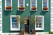 Elegant harbourside house with pair of olive trees and geraniums in window boxes on seafront in Gorey, Jersey, Channel Isles