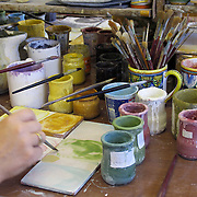 Hand holding paint brush dips into fresh paint in the process of painting ceramics designs ceramics factory in Deruta, Italy