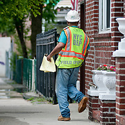 May 6, 2010 - A ruprured underground water main was the latest in what has become a series of misfortunes to befall the residents of Coreal Avenue since construction began on 3050 Corlear Ave.  DEP employee George Ortiz walks door to door, distributing emergency water shut-off notices.