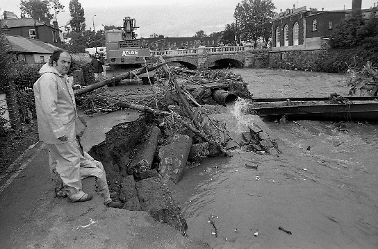 "Flooding at the Dodder..1986..26.08.1986..08.26.1986..28th August 1986..As a result of Hurricane Charly (Charlie) heavy overnight rainfall was the cause of severe flooding in the Donnybrook/Ballsbridge areas of Dublin. In a period of just 12 hours it was stated that 8 inches of rain had fallen. The Dodder,long regarded as a ""Flashy"" river, burst its banks and caused great hardship to families in the 300 or so homes which were flooded. Council workers and the Fire Brigades did their best to try and alleviate some of the problems by removing debris and pumping out some of the homes affected..Note: ""Flashy"" is a term given to a river which is prone to flooding as a result of heavy or sustained rainfall...Picture shows work men at the site where the road had subsided near the bridge over the Dodder at Ballsbridge, Dublin.The picture also shows damage to a water main."