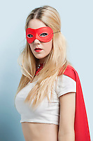 Portrait of young woman wearing superhero costume against blue background