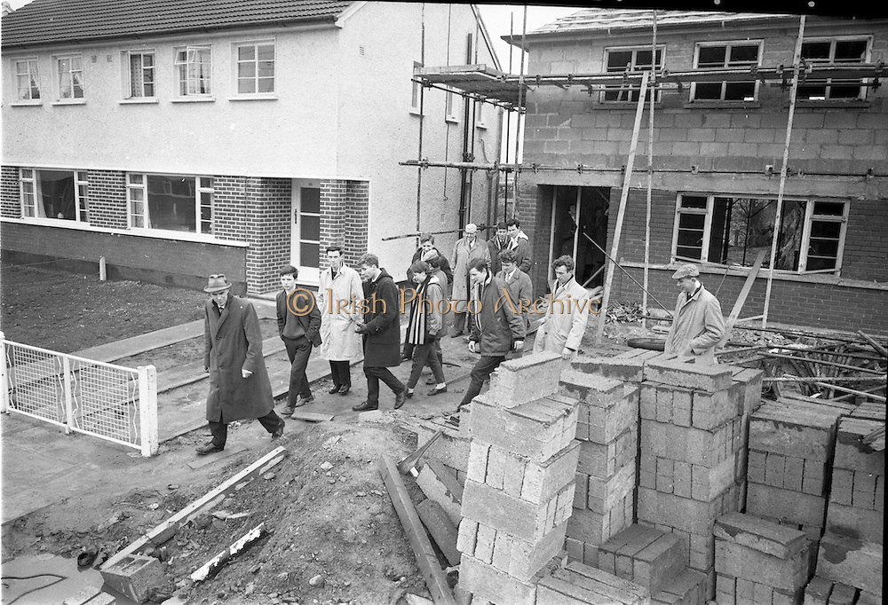 """01/04/1963<br /> 04/01/1963<br /> 01 April 1963<br /> Students from Bolton Street College of Technology visit """"Greenfield"""" (Wates) Housing Estate at Ballymun, Dublin.  Mr George Madden, storekeeper at Wates Greenfield Estate and Mr. William Gilligan, B.A., M.R.I.A.I., showing a group of students around the estate."""