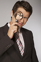 Young caucasian businessman with magnifying glass