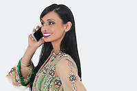Beautiful young Indian woman in traditional wear attending phone call over gray background