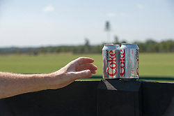 detail of a man's hand about to grab a diet coke outdoors