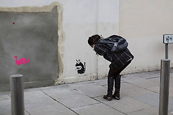 © licensed to London News Pictures. London, UK 22/02/2013. A woman looking at the graffitis thought to be Banksy's new work appears at the site of 'stolen' mural in Turnpike Lane, next to a Poundland branch. Photo credit: Tolga Akmen/LNP