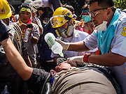 26 DECEMBER 2013 - BANGKOK, THAILAND: Medics work on a man who was shot with a rubber bullet by Thai riot police. Thousands of anti-government protestors flooded into the area around the Thai Japan Stadium to try to prevent the drawing of ballot list numbers by the Election Commission, which determines the order in which candidates appear on the ballot of the Feb. 2 election. They were unable to break into the stadium and ballot list draw went as scheduled. The protestors then started throwing rocks and small explosives at police who responded with tear gas and rubber bullets. At least 20 people were hospitalized in the melee and one policeman was reportedly shot by anti-government protestors.      PHOTO BY JACK KURTZ