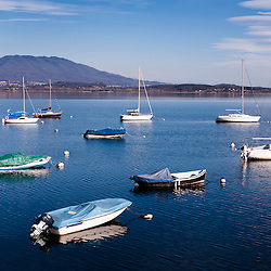 Boats anchored in a tranquil bay on Lake Maggiore, Italy