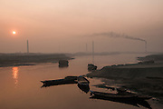 Bangladesh, waterway west of Dhaka at sunrise, with brick kiln factory smokestacks.