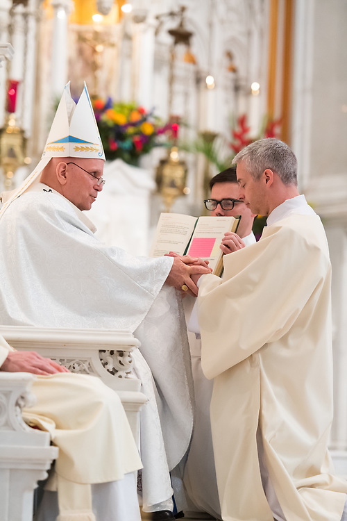DENVER, CO - MAY 13: Denver Archbishop Samuel Aquila holds Peter Wojda's hands for the promise of respect and obedience for his ordination of the priesthood at the Cathedral Basilica of the Immaculate Conception on May 13, 2017, in Denver, Colorado. (Photo by Daniel Petty/for Denver Catholic)