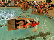 "Breanna Pokrzywa,17, left, and Chris Pawlowski,18, in their boat the ""USS PDS,"" (Please Don't sink), do just that at the 2nd annual Cardboard Boat Regatta at Greendale High school, 6801 Southway, Greendale, Wednesday evening. Thirty two boats were entered in the competition using Cardboard and packing tape. JEFFREY PHELPS"