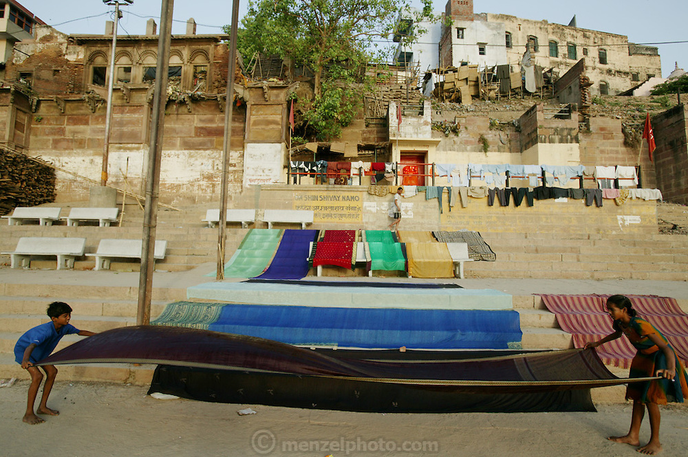 Children put out just-washed fabric to dry in the sun near the cremation grounds at Harishchandra Ghat.