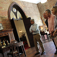 St. John's Episcopal Church member Wendy Frederick, left, tells a group of Milan, Tennessee visitors about the church's old parish hall.