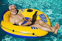 Senior Man lying on inflatable raft using laptop elevated view portrait.