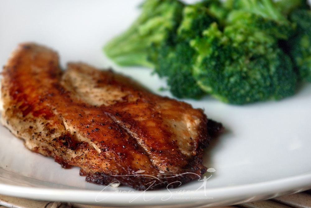 Pan-seared tilapia is served with a side of steamed broccoli. (Photo by Carmen K. Sisson/Cloudybright)