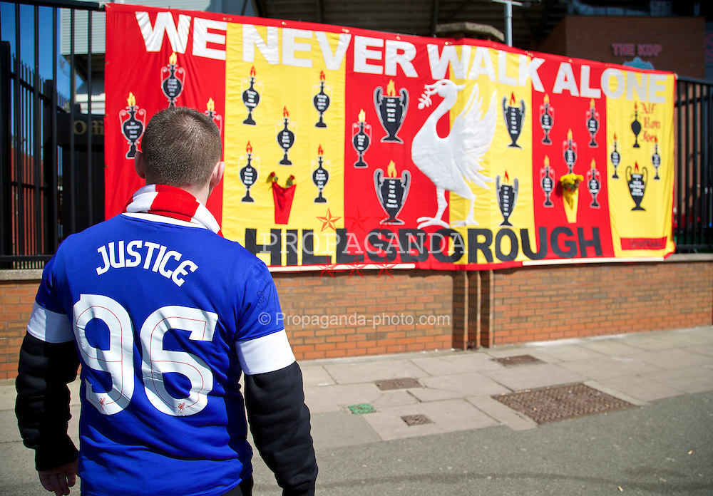 LIVERPOOL, ENGLAND - Tuesday, April 15, 2014: An Everton supporter looks on at a large banner with the names of the 96 victims of the Hillsborough Disaster embodied before the 25th Anniversary Hillsborough Service at Anfield. (Pic by David Rawcliffe/Propaganda)