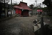 Le temple en arrière plan se trouvait face au escalier du premier plan. Il fu araché et transporté par la vague jusqu'à ce qu'il soit arrêté par un arbre et le torii.
