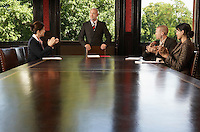 Businesspeople around boardroom table applauding man