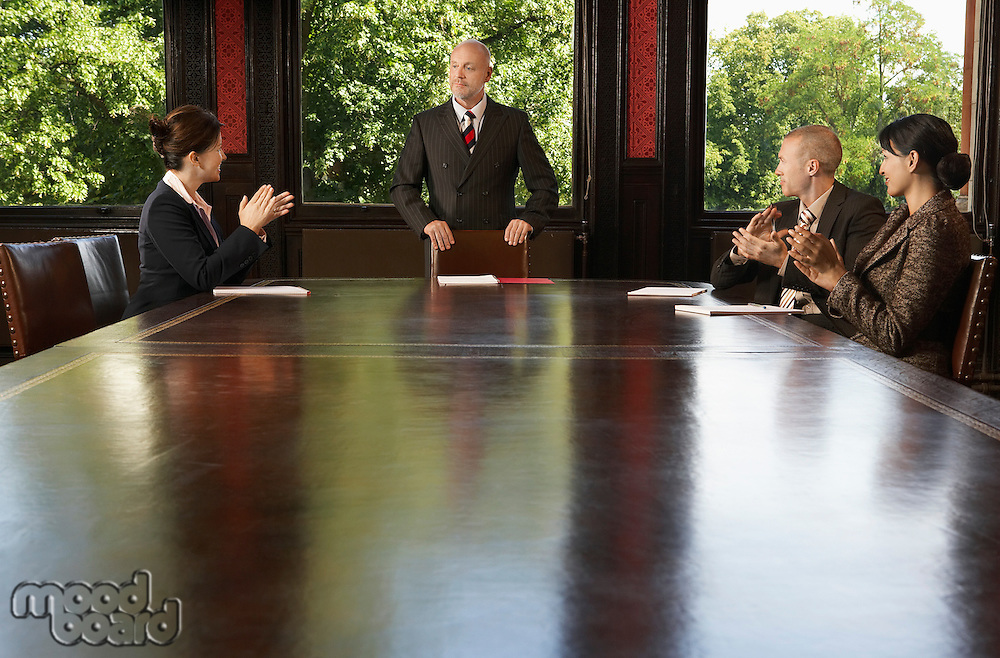 Businesspeople around boardroom table applauding man