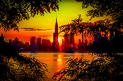 A fiery sun sets behind the Empire State Building and the New York skyline as seen from across the East River and framed by leafy trees.