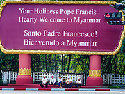 27 NOVEMBER 2017 - YANGON, MYANMAR: Men sitting under a sign welcoming Pope Francis to Myanmar wait to see the Pontiff. Francis Pope Francis arrived in Yangon Monday for a four day / three night visit. Tuesday he is going to the capitol, Naypyidaw (Nay Pyi Taw) to meet with Aung San Suu Kyi and other Myanmar leaders. Wednesday and Thursday he is saying mass in Yangon and on Thursday afternoon he is going to neighboring Bangladesh. There are around 450,000 Catholics in Burma, about 1% of the total population.   PHOTO BY JACK KURTZ