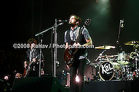 Kings of Leon performing at Madison Square Garden on January 29, 2009. .Caleb Followill -  beard, wearing a grey t-shirt and black vest. (lead singer/rhythm guitar. Nathan Followill (drums/backup vocals).Jared Followill - (bass guitar/backup vocals/synthesizer.                          Matthew Followill - wearing black leather jacket   (lead guitar/backup vocals).