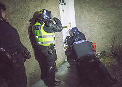 Police take part in an operation against drug dealers in the Stirling area early this morning. Pic of them forcing open a door.