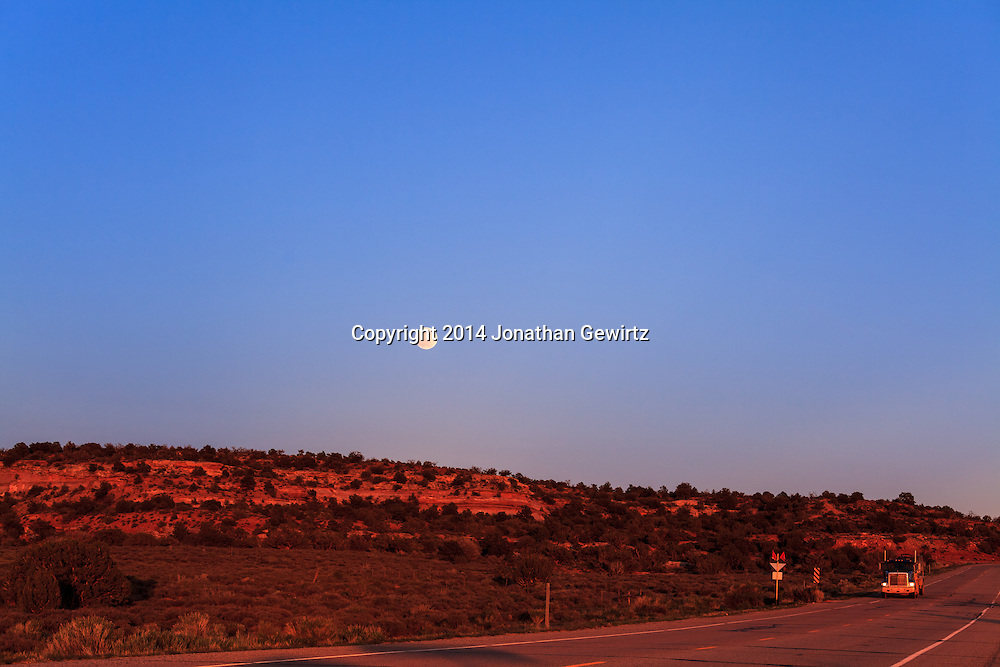 The full moon rises over desert hills glowing red in the last rays of the setting sun, adjacent to Utah Highway 313 on the high plateau northwest of Moab.<br />