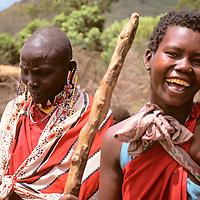 Africa, Kenya, Maasai Mara. Two Maasai women enjoy demonstrating the building of a home (traditionally built by the women) in their boma at Olanana in the Maasai Mara.