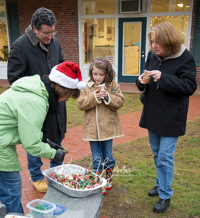 Carol Gerken from the Greater Meredith Program along with Bob Moran, Abigail Seal and Lois Moran warm up with a cup of hot cocoa prior to decorating the Christmas tree in Meredith Park with homemade ornaments made by family and friends at the Meredith Library.  (Karen Bobotas/for the Laconia Daily Sun)