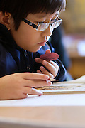 Seattle, Washington: March 20, 2008. A middle school student from Thailand, with pencil and eraser in hand, concentrates during his first day in class at Seattle's transitional school for immigrant secondary school students. MR-BOC08-067 ©Stefanie Felix