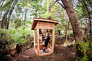 Spring 2012:  Canadian writer Susan Musgrave poses in a glass outhouse on her property in Haida Gwaii.