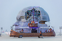 """Mutant Vehicle (name unknown) and the Head Maze<br /> <br /> Head Maze<br /> by: Matthew Schultz and The Pier<br /> from: Reno, NV<br /> year: 2019<br /> <br /> The Head Maze is a purposeful juxtapositions of two forms, a peaceful meditative reflection and our inevitable struggle with the nature of cognition; a monolithic mind caught in time between multiple selves. The head towers four stories over the playa floor, encased in mulberry paper and epoxy modeled after the work of Yoshio Ikezaki. The head rests in repose while its left hand claws at its mind fighting to reveal a crystalline stained glass structure akin to the """"Space Whale"""" inside.<br /> <br /> A series of hidden doors in the mouth, wrists and head open into a four story, 18 room maze. Each modular room creates a unique space dedicated to the nature of our minds, our struggles with being and the weird and fanciful process of dreaming.<br /> <br /> URL: http://www.headmaze.com<br /> Contact: headmaze2019@gmail.com<br /> <br /> https://burningman.org/event/brc/2019-art-installations/?yyyy=&artType=B#a2I0V000001AVtbUAG"""
